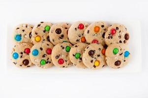 Cookies aux bonbons multicolores sur une plaque rectangulaire blanche