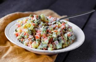 salade traditionnelle russe olivier aux petits pois dans l'assiette photo
