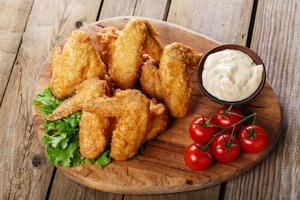 ailes de poulet frites avec sauce et tomates photo