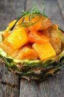 poulet cuit à l'ananas servi dans un bol d'ananas