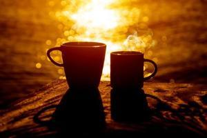 silhouettes de café du matin sur le lac. photo