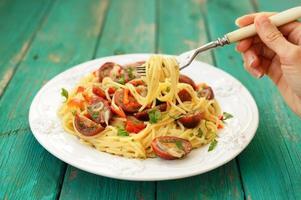 spaghetti al pomodoro en plaque blanche avec main tenant