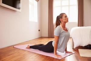 femme, faire, yoga, fitness, exercices, sur, natte, dans, chambre à coucher photo