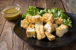 tofu frit mangé avec sauce photo
