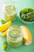 Smoothie vert sain avec banane mangue épinards dans des bocaux en verre photo