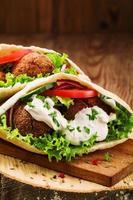 falafel et légumes frais dans du pain pita sur table en bois photo