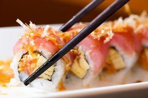 rouleau de sushi avec des baguettes noires
