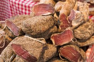 jambon de poivre vendu à la coupe sur un étal de marché. photo
