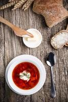 soupe savoureuse avec du pain sur un fond en bois.