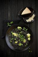 spaghetti à l'encre de seiche avec brocoli et pois verts. photo