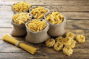 Vue de dessus divers types de pâtes italiennes fond rustique photo