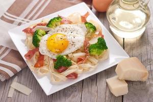 pâtes tagliatelles au brocoli, prosciutto et œuf au plat. photo