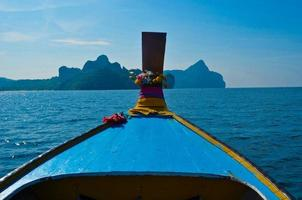 bateau longtail naviguant dans l'île de phiphi, thaïlande