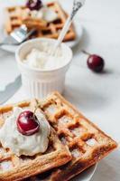 petit déjeuner avec gaufres complètes et crème fouettée photo