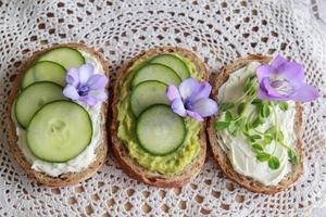 Sandwichs au visage vert au levain avec fleurs comestibles violettes