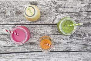Divers smoothies aux fruits colorés dans des bouteilles en verre