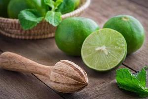 presse-fruits en bois et citron vert sur table