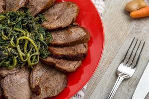 rôti tranché avec un côté de légumes verts photo