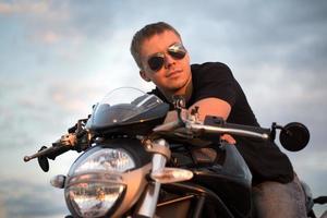Portrait romantique bel homme motard est assis sur un vélo photo