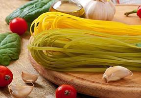 Pâtes fettuccine colorées et ingrédients de cuisine sur table en bois