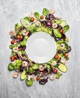 salade de crevettes à la laitue autour d'une assiette vide blanche photo