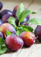 délicieuses prunes bleu-orange avec des gouttes d'eau photo