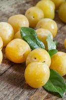 prunes jaunes mûres sur fond de bois ancien photo