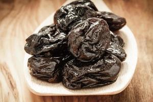 prunes séchées pruneaux sur une cuillère en bois photo