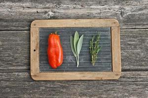 tomates et herbes sur la tablette d'écriture ardoise photo