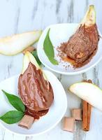 tranches de poire au chocolat dans des bols sur une table en bois photo