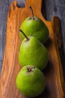 poires sur planche à découper en bois et table en bois ancienne
