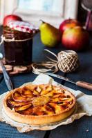 tarte aux pommes sur fond de sable avec poire, caramel photo