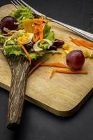salade de maïs et cuillère de table noire sur le sol.
