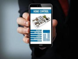 Smartphone homme d'affaires de contrôle de maison intelligente en ligne photo