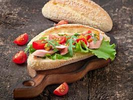 sandwich avec saucisse, laitue, tomate et roquette