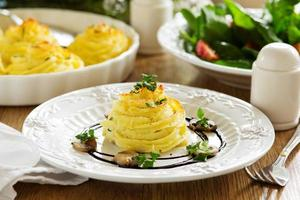 viande cuite au four avec des champignons en purée de pommes de terre.