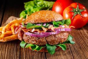 burger avec bacon et frites se bouchent. photo