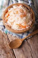 chou aigre et carottes dans une assiette en bois. vue de dessus verticale