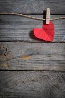 coeur rouge accroché à la corde à linge. sur fond de bois ancien.