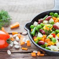 Repas de légumes mélangés dans la vieille poêle à frire gros plan et ingrédients photo