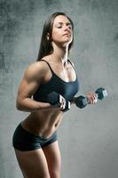 belle femme musclée sportive avec deux haltères photo