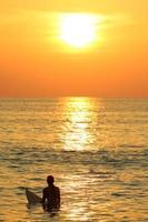fille de surfeur au coucher du soleil photo