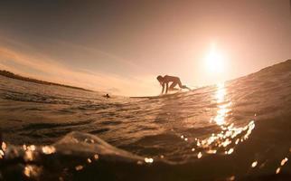 la fille avec surf au lever du soleil photo