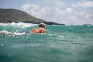 homme nager le surf dans la vue arrière de la mer