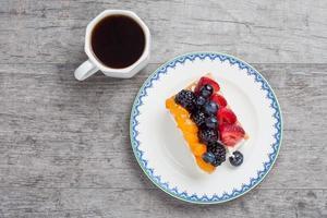 tarte aux fruits sur une assiette servie avec du café