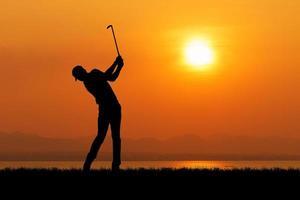 silhouette de golfeur contre le coucher du soleil photo