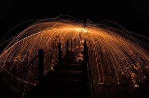 l'homme a coulé de la laine d'acier de feu sur le pont photo
