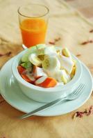 salade de fruits frais mélangés avec du yaourt et du jus d'orange