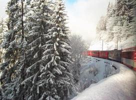 Train suisse voyageant à travers les Alpes en hiver