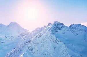 montagnes couvertes de neige d'hiver au coucher du soleil photo